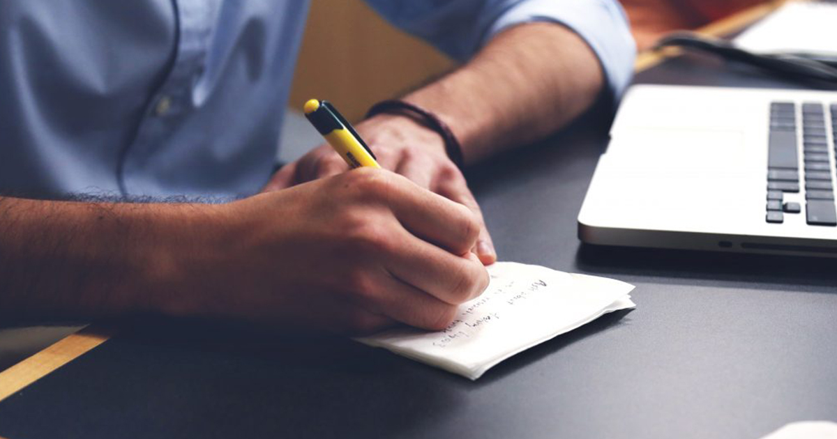 person writing on the paper to increase the writing skills